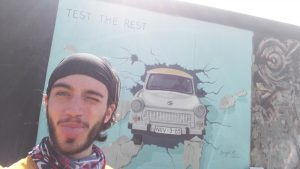Picture: David, our summer student, in front of the Berlin wall.