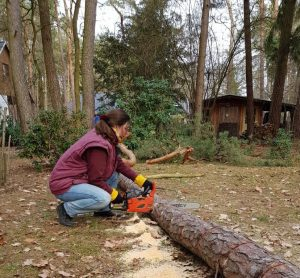 Erika in the forest, working with a chain saw.
